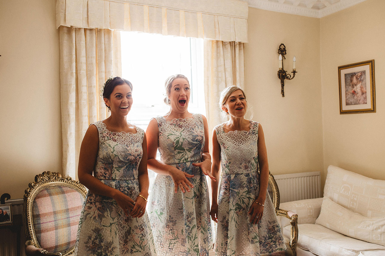 three bridesmaids look on and have suprised expressions in a livingroom