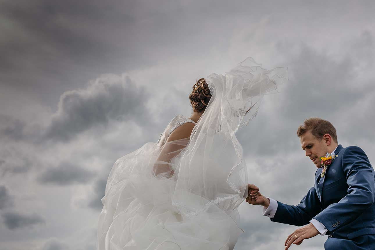 a groom helps a bride over a wall whilst her dress blows in the wind