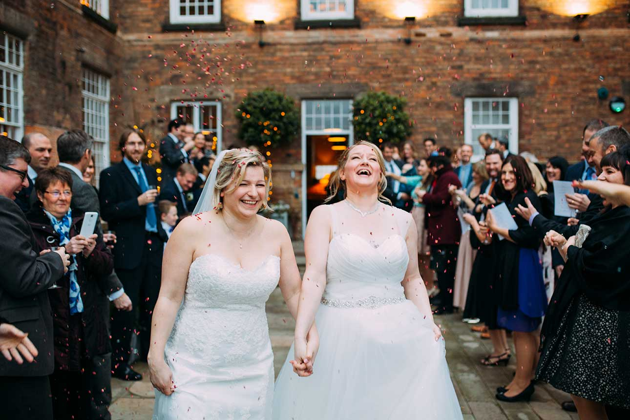 two brides laugh and hold hands as wedding guests through confetti at them