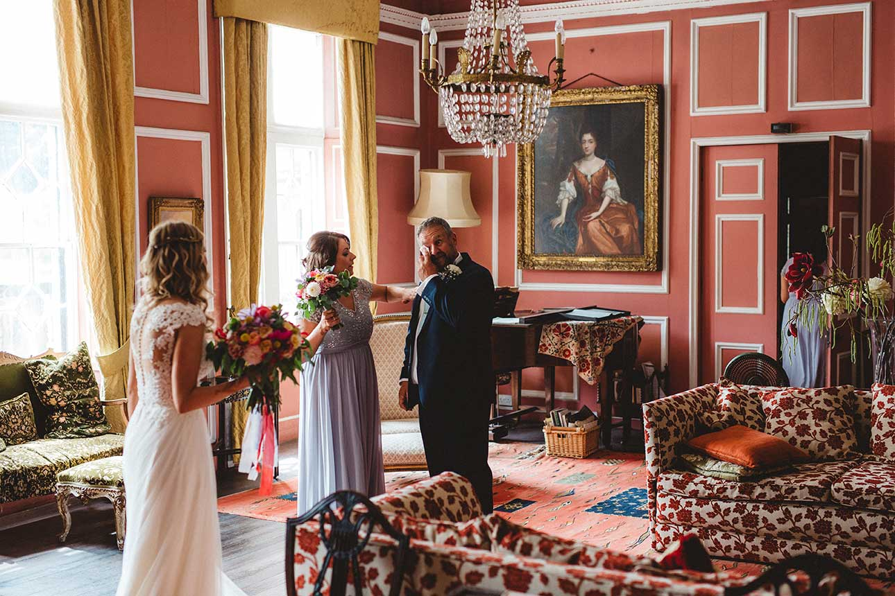 a father wipes a tear away as he looks at his daughter in a grand room before she gets married at thrumpton hall